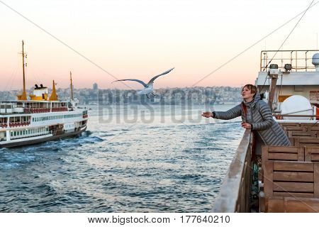 Woman feeding Sea Gulls from Board of Tourist Boat floating across Harbor of City soft sunrise colors of Sky and Urban landscape on Background