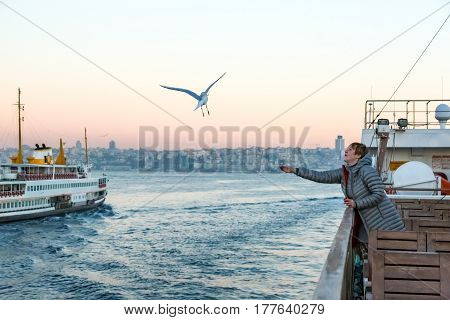 Sea Gull flying following passenger Vessels and young Woman watching its flight staying on board of Boat travelling across Bosphorus channel in Istanbul city