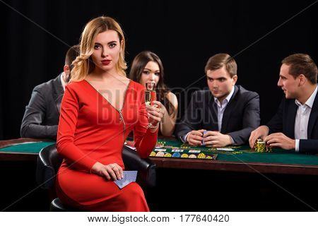 Young people playing poker at the table. Luxury women in dresses with a glass of champagne in hand sitting in the foreground. Casino