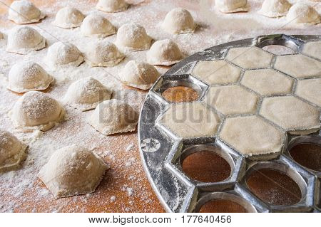 Step by step process of making home-made dumplings, ravioli or pelmeni with minced meat filling using ravioli mold or ravioli maker. Ready for cooking raviolis on wooden board