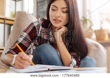 New ideas. Delighted attractive creative woman holding a pencil and noting something down while holding her chin