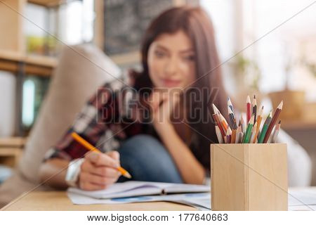 Designers workplace. Selective focus of colored pencils standing on the table with a beautiful positive young woman writing in her notebook in the background