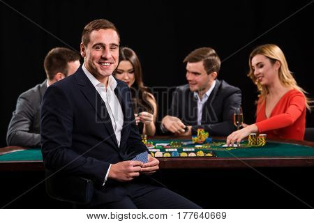Young people playing poker at the table. Handsome man with cards in hand sitting in the foreground. Casino
