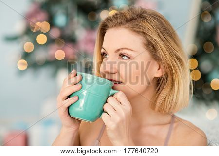 Beautiful yourng woman with a cup of coffe in her hands with blured background looking away from camera