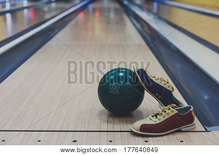 Bowling accessories background with copy space. Interior of bowling alley, lane with ball and special shoes