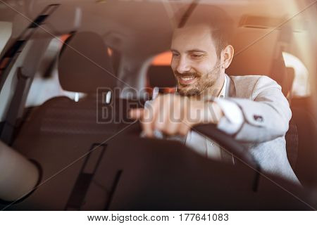 Handsome cute businessman driving car before buying