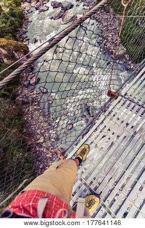Backpacker crossing suspension bridge and looking down at the river in Himalayas Nepal. Trekking and hiking with backpack in high mountains. Annapurna Circuit Trek Autumn season in Nepal Asia.