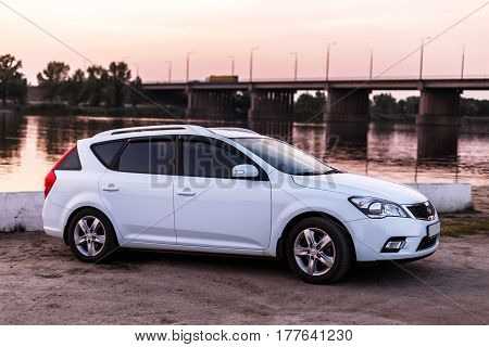 NOVOSELIVKA DNIPROPETROVSK REGION UKRAINE - SEPTEMBER 01 2015: KIA CEED WAGON WHITE COLOR NEAR THE SAMARA RIVER WITH BRIDGE IN TWILIGHT