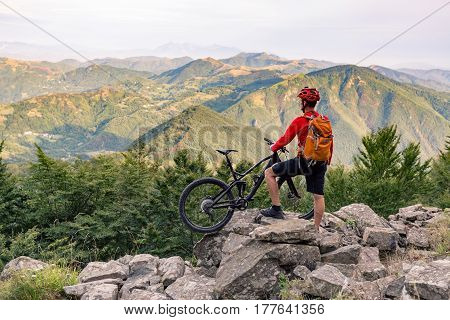Mountain biker looking at beautiful inspirational landscape view on bike trail in autumn mountains. Rider cycling on rocky single track. Sport fitness motivation and adventure inspiration.