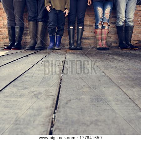 People Wearing Boots Standing Together on Wooden Floor