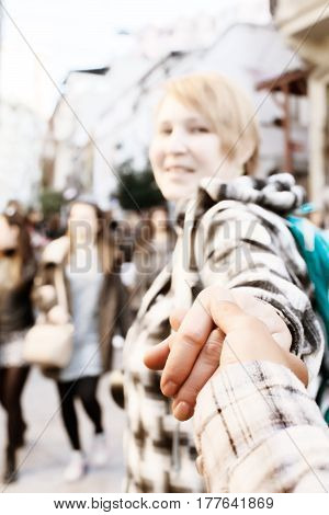 Cute excited Woman pulling someone hand and walking toward crowded city street. Casual clothing, blurred unrecognisable face