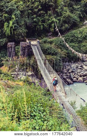 Woman backpacker crossing suspension bridge in Himalayas Nepal. Trekking and hiking with backpack in high mountains. Annapurna Himal Range on Annapurna Circuit Trek. Autumn season in Nepal Asia.