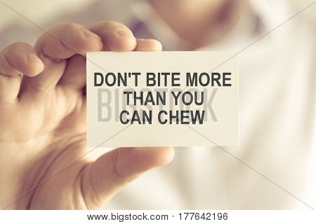 Businessman Holding Dont Bite More Than You Can Chew Message Card