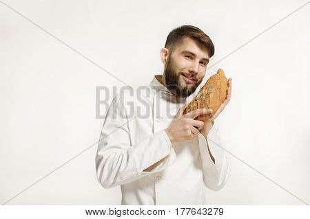 Handsome smiling BAKER smelling a freshly baked loaf in the kitchen of the bakery. Handsome smiling BAKER smelling a freshly baked loaf on white background.