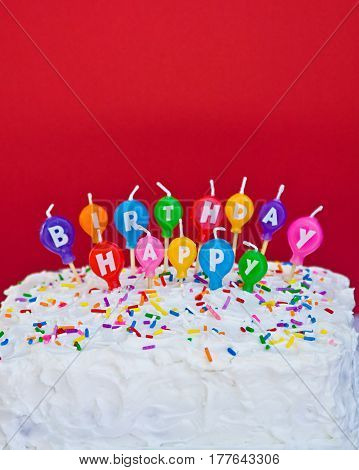 Homemade square cake with white frosting, sprinkles and happy birthday balloon candles on a red background