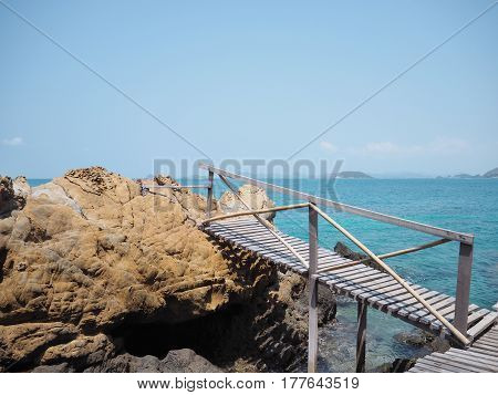 temporary wooden bridge across water on the summer beach