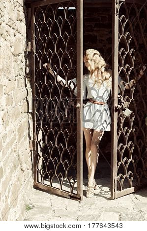 A young woman in short modern dress holds her hands behind the bars the door in an old stone fortress
