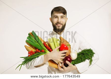 Smiling handsome chef with vegetables in hands isolated on white background. VEGAN FOOD. Portrait of happy professional chef with vegetables and herbs.