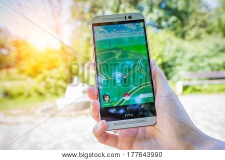 Belchatow Poland - July 22 2016: HTC One M9 held in one hand showing its screen with Pokemon Go application. In the background blured park.