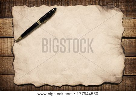 Notepaper and pen on wooden backgroundConcept filter sepia