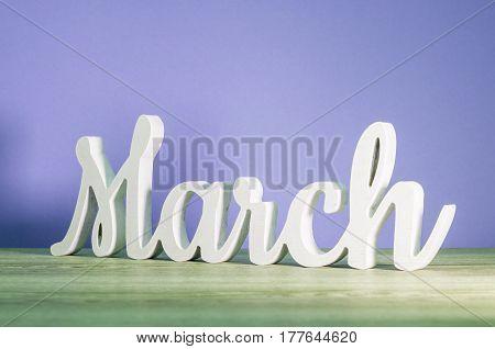March - biginning of springtime concept. Wooden carved inscription on purple or dark pink background.