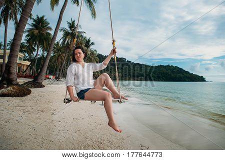 Woman sit on Swing tropical beach phu quoc