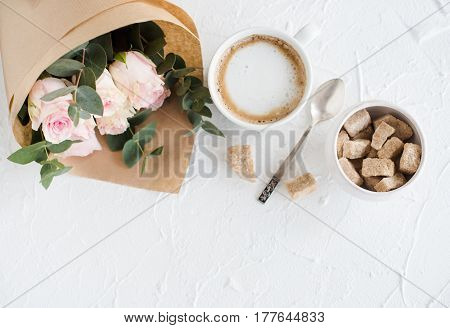 Romantic feminine background with coffee and roses on white textured tabletop, elegant light flatlay