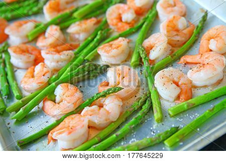 Fresh asparagus with shrimp on a baking sheet with coarse salt olive oil and black pepper