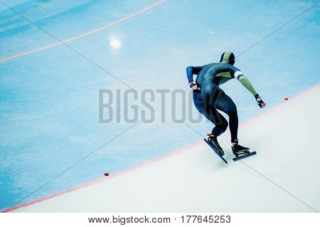 male athlete speed skater on turn ice arena