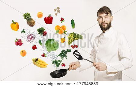Handsome professional chef in uniform uggling with vegetables and other food in the kitchen. Chef and flying vegetables and fruits osilated on white background. Fruits with vegetables and utensils
