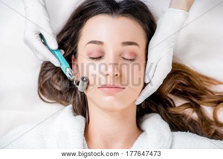 Making dry needlying procedure on woman's face in the cosmetology office poster