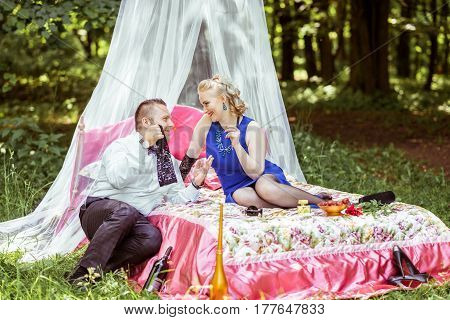 Man and woman sitting on the bed in the lawn and man undressing woman in Lviv, Ukraine.