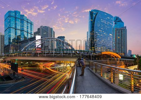 Photographer take a photo at bridge link between mrt and bts mass transportation in heart of bangkok modern important landmark of city life in Bangkok Thailand. Sathorn is business area of Thailand