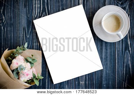Dark styled background with coffee, smartphote, roses and magazine cover mock-up on black wooden tabletop, blogger workspace