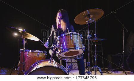 Emotional girl drummer, attractive youngblack hair model plays the drums, wide angle
