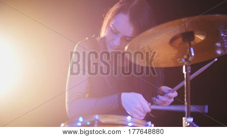 Teen garage rock music - attractive girl percussion drummer perform music break down, horizontal