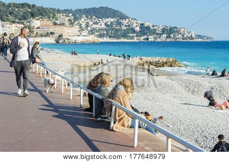 Nice, France - 25 February, Tourists on the waterfront, 25 February, 2017. People and tourists having a rest on the Cote d'Azur.