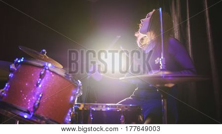 Teen rock music - girl with flowing hair percussion drummer performing with drums, close up