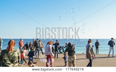 Nice, France - 25 February, People have fun with soap bubbles, 25 February, 2017. People and tourists having a rest on the Cote d'Azur.