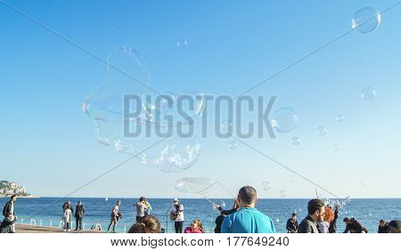 Nice, France - 25 February, Soap bubbles above the heads of people, 25 February, 2017. People and tourists having a rest on the Cote d'Azur.