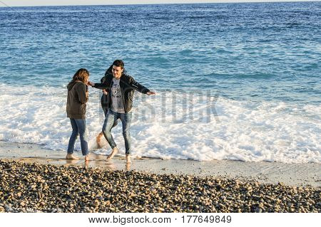 Nice, France - 25 February, Young people on the shore, 25 February, 2017. People and tourists having a rest on the Cote d'Azur.