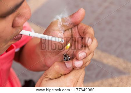 Man holding burning cigarette in hand, Smoking Man on Street.