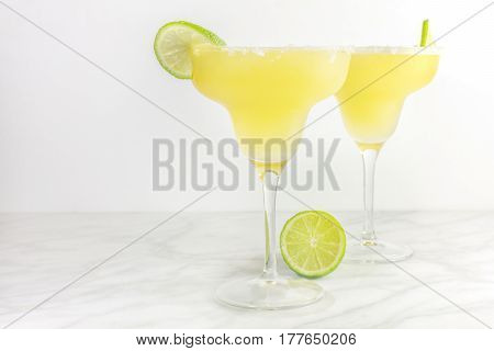 Lemon Margarita cocktails with wedges of lime, with a place for text