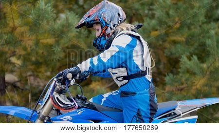 Girl mx biker - motocross racer on dirt bike at sport track, telephoto