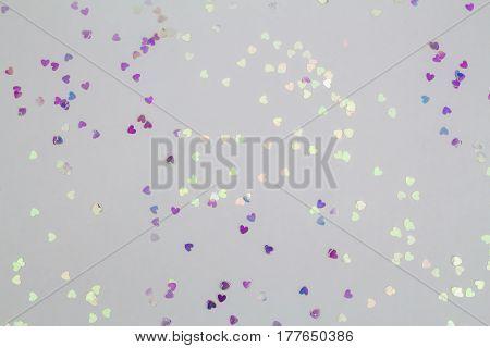 A shiny sparkly mini heart confetti background