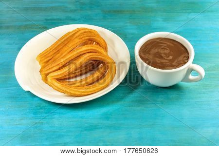A plate of churros, traditional Spanish, especially Madrid, dessert, particularly for Sunday breakfast, with a cup of hot chocolate, on a vibrant turquoise table with a place for text