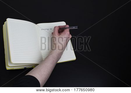 A writer writing the words encourage me in a lined notebook