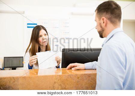 Receptionist Explaining Services To Patient