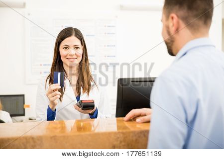 Cute Receptionist Taking Credit Card Payment