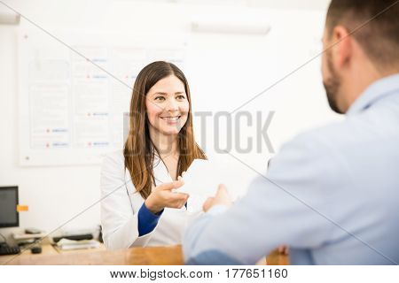 Receptionist Handing Results To Patient